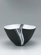 写真:Black bowl with white earthen glaze.