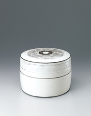 写真:Covered circular box with white slip and line design.