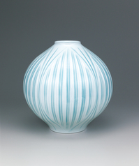 写真:White porcelain flower vase with pale blue glaze and engraved design.