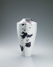 写真:Faceted flower vessel with wild grape design.