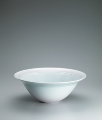 写真:Large white porcelain bowl with pale blue glaze, red decoration and stream design.