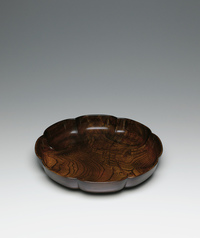 写真:Flower-shaped food vessel of zelkova wood finished in wiped urushi.