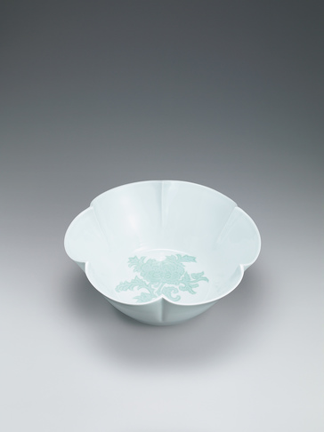 image White porcelain flower-shaped bowl with green glaze and engraved peony design.