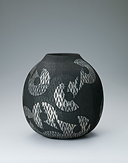写真:Vessel with matte black glaze and geometrical design over diamond pattern.