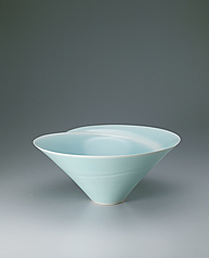 写真:Large white porcelain bowl with pale blue glaze and blurred white decoration.