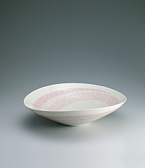 写真:White porcelain bowl with pale yellow glaze and wave design.