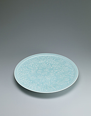 写真:Large white porcelain dish with pale blue glaze and design of flowers looming in dusk.
