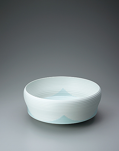 写真:White porcelain bowl with pale blue glaze and glaze decoration.
