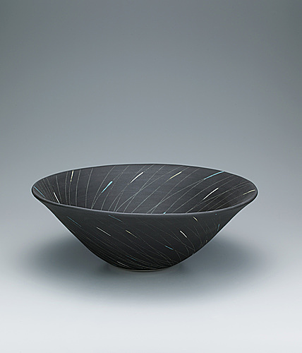 写真:Bowl with line design in colored clay on dark blue background.