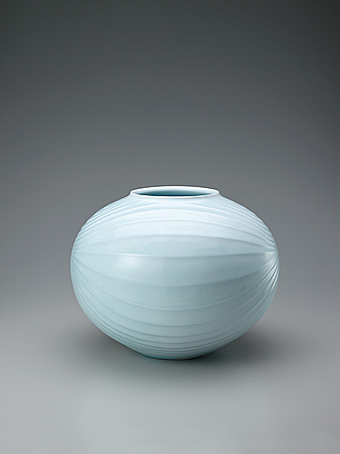 写真:White porcelain jar with pale blue glaze and curved line design.